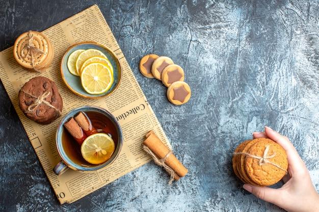 暗い背景に古い新聞にシナモン入りの紅茶のカップを持つおいしいクッキーと手の平面図