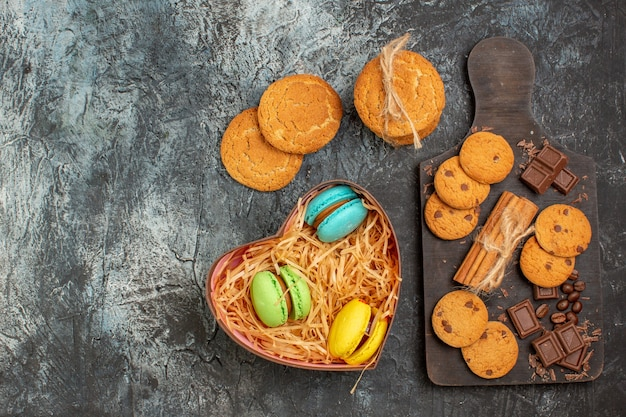 氷のような暗い背景の上のハート型のボックスにおいしいクッキーチョコレートバーとマカロンの上面図