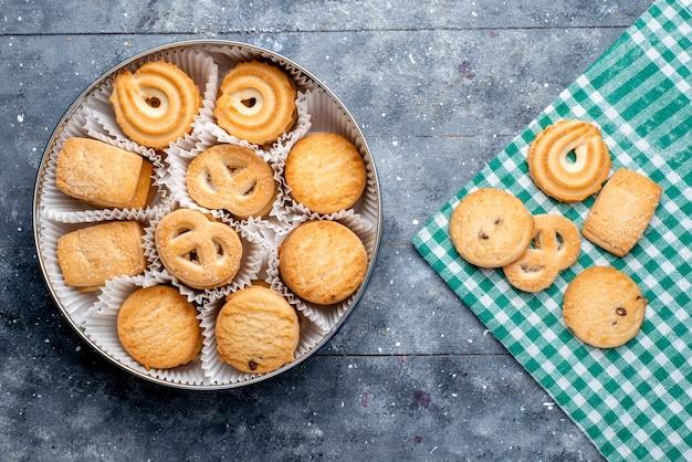 灰色の机の上の丸いパッケージの中に形成された異なるおいしいクッキーの上面図、砂糖の甘いケーキビスケットクッキー