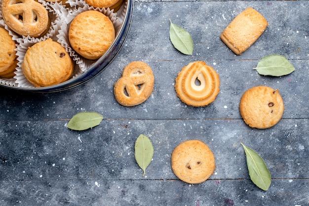 灰色の机の上の丸いパッケージの中に形成された異なるおいしいクッキーの上面図、甘いケーキビスケットクッキー