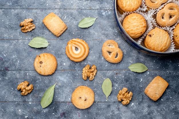 Вид сверху вкусного печенья различной формы внутри круглой упаковки с грецкими орехами на сером столе, сахарного сладкого печенья