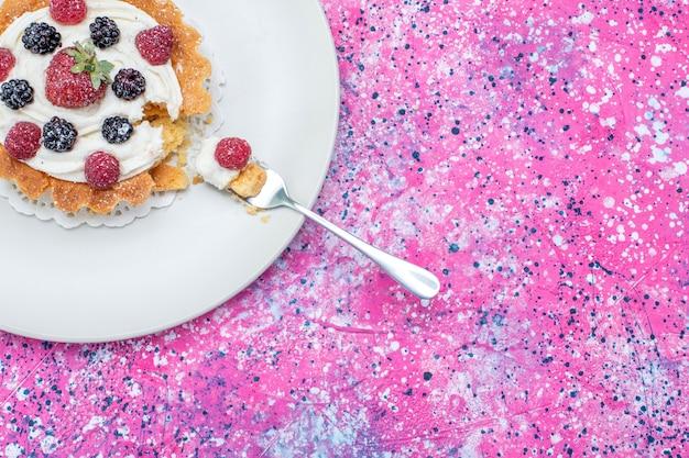 Вид сверху вкусного сливочного торта с разными свежими ягодами внутри белой тарелки на ярком столе, ягодный свежий кислый