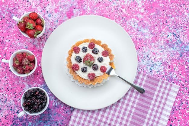 明るい光の机の上にさまざまな新鮮なベリー、ベリーフルーツの新鮮な酸味のあるおいしいクリーミーなケーキの上面図