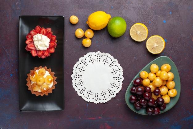 暗い表面に新鮮なレモンとフルーツが入ったプレート内のおいしいクリーミーなケーキの上面図
