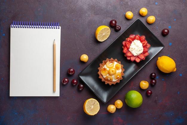 新鮮なレモンのメモ帳と暗い表面の果物とプレート内のおいしいクリーミーなケーキの上面図