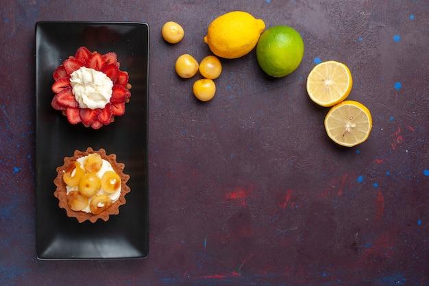 暗い表面に新鮮なレモンとプレート内のおいしいクリーミーなケーキの上面図