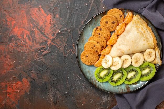 Вид сверху вкусного крепа нарезанного цитрусового печенья на темном полотенце смешанного цвета