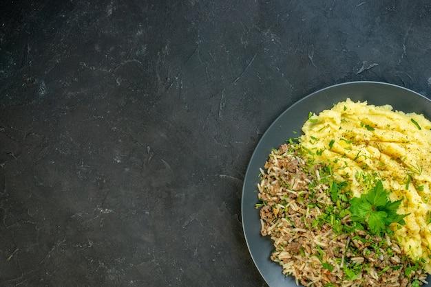 Вид сверху вкусного ужина с картофельным пюре и мясом на тарелке слева на черном фоне со свободным пространством