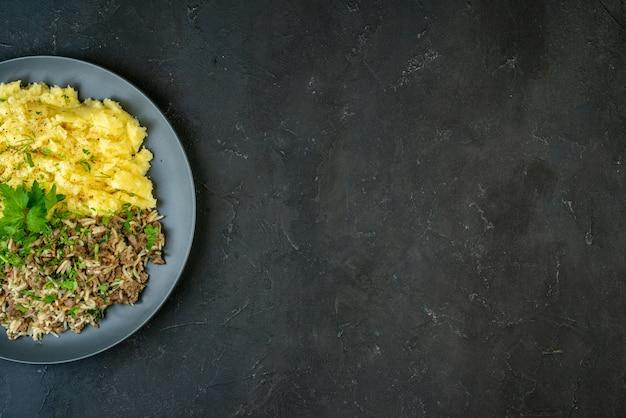 Вид сверху вкусного ужина с картофельным пюре и мясом на тарелке с правой стороны на черном фоне со свободным пространством