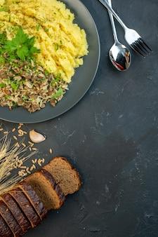 Вид сверху вкусного ужина с мясом и картофельным пюре на серой тарелке, ломтики хлеба, набор столовых приборов с чесночным шипом на черном фоне