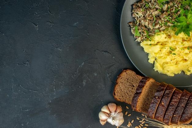 Вид сверху на вкусный ужин с мясом и картофельным пюре на серой тарелке, ломтики хлеба, чеснок на черном фоне