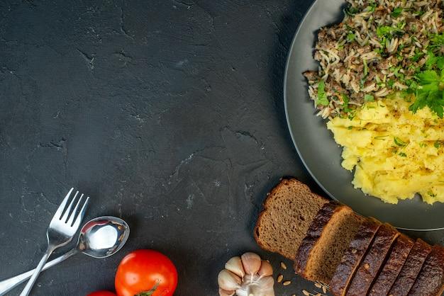 Вид сверху вкусного ужина с мясом и картофельным пюре на серой тарелке, ломтики хлеба, чеснок, помидоры, столовые приборы, набор на черном фоне