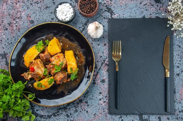 Вид сверху вкусного ужина с мясным картофелем, подаваемым с зеленым в черной тарелке и набором столовых приборов на разделочной доске, цветочных специй, чеснока на фоне смешанных цветов