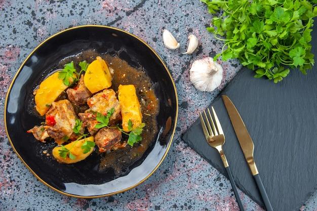 Вид сверху на вкусный ужин с мясным картофелем, подаваемым с зеленым в черной тарелке и набором столовых приборов на разделочной доске с чесноком на фоне смешанных цветов