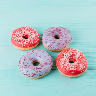 Top view of delicious donut with sprinkles on wooden table