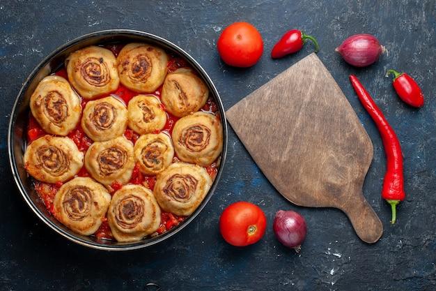 鍋の中に肉が入ったおいしい生地の食事と、暗い机の上の玉ねぎ、トマト、ピーマン、食品の食事の肉野菜などの新鮮な野菜の上面図