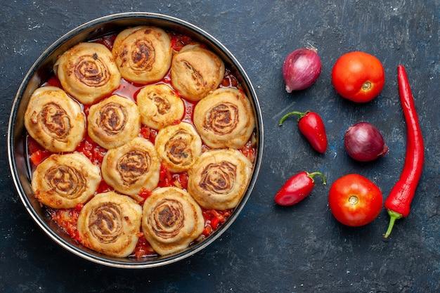 鍋の中のおいしい生地の肉と、暗い机の上の玉ねぎ、トマト、ピーマン、食用肉骨粉などの新鮮な野菜の上面図