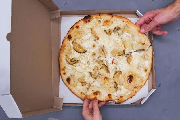 段ボール箱のおいしい4つのチーズのピザのトップビュー