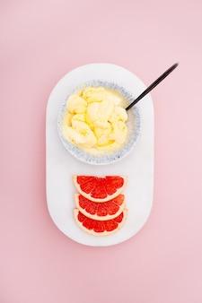 Вид сверху вкусных свежих грейпфрутов и персикового мороженого на розовом