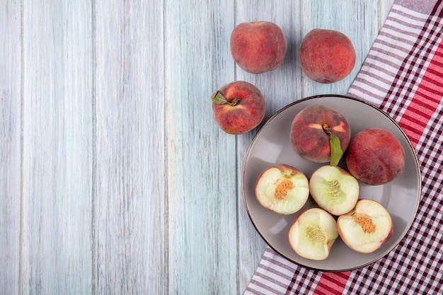 灰色の木のプレートにおいしい新鮮なジューシーな桃のトップビュー