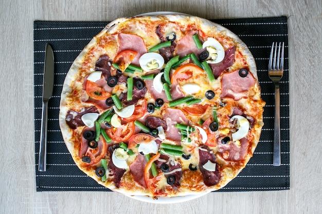 豆、チーズ、ハム、卵とおいしい新鮮なピザの上面図