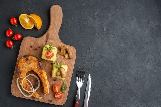黒い表面にセットされた木製のまな板カトラリーのおいしい揚げ魚料理とマッシュルームトマトグリーンの上面図