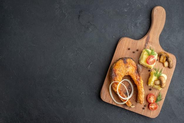 黒い表面の左側にある木製のまな板においしい揚げ魚の食事とキノコのトマトグリーンの上面図