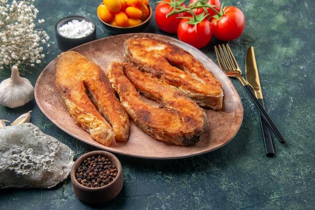 茶色のプレートとカトラリーセットのおいしい揚げ魚の上面図は、空きスペースのあるミックスカラーテーブルにスパイス食品を設定します