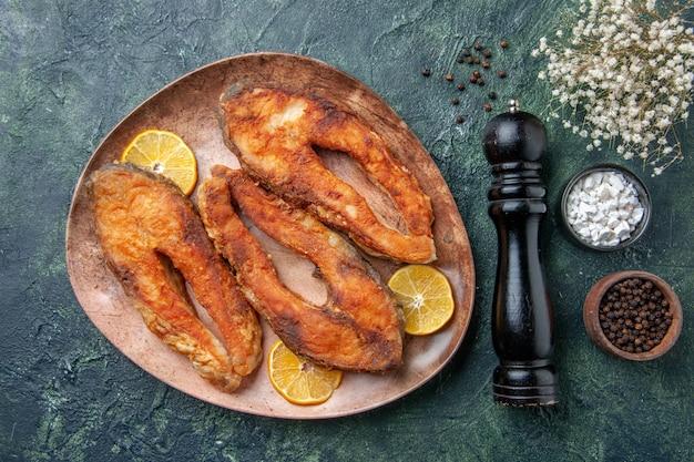 自由空間のあるミックスカラーテーブルの茶色のプレートスパイスのおいしい揚げ魚とレモンスライスの上面図
