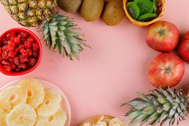 Вид сверху вкусных фруктов на розовой поверхности