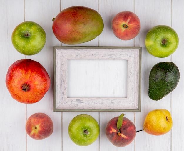 Вид сверху на вкусные фрукты, такие как гранат, яблоко, манго, груша, персик, изолированные на белом с копией пространства