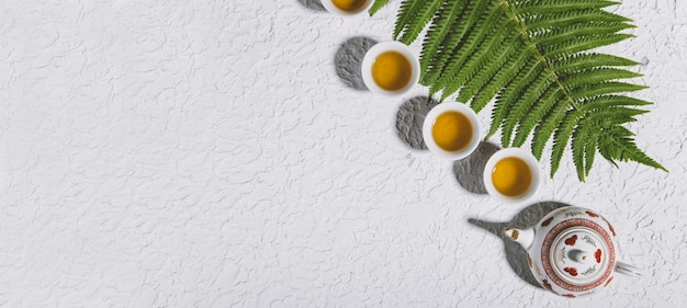 흰색 콘크리트 배경에 있는 맛있는 허브 티 세트의 평면도