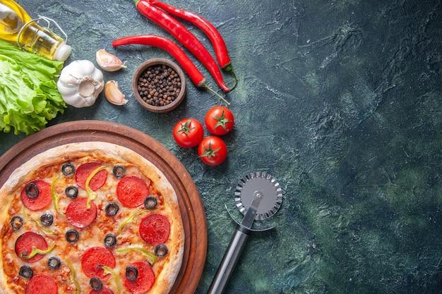 木製のまな板トマトケチャップニンニクペッパーオイルボトルグリーンバンドルの暗い表面のおいしい自家製ピザの上面図