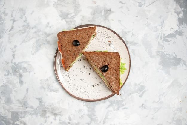 ステンドグラスの白い表面の青いトレイにおいしい自家製サンドイッチの上面図