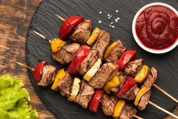 Вид сверху вкусного шашлыка на сланце с салатом и кетчупом