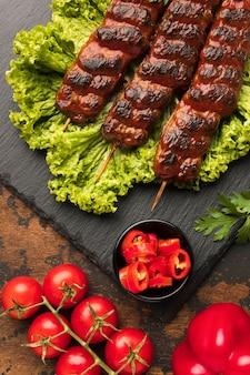 Вид сверху вкусного шашлыка на сланце с салатом и помидорами