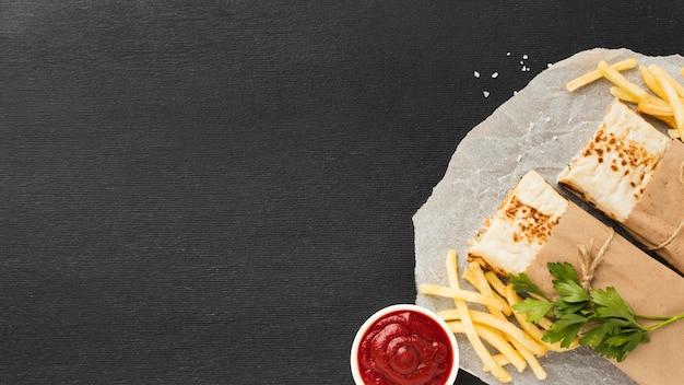 Вид сверху вкусного кебаба с кетчупом и картофелем фри