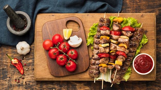 Вид сверху вкусного кебаба с мясом и овощами на разделочной доске