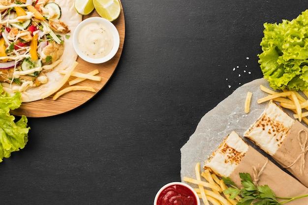 Вид сверху вкусного кебаба с салатом и картофелем фри