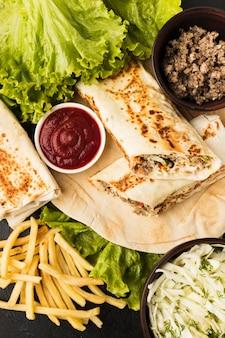 Вид сверху вкусного шашлыка с салатом и кетчупом