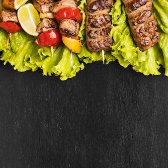 Вид сверху вкусного шашлыка с салатом и мясом