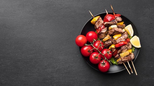 Вид сверху вкусного шашлыка с помидорами и копией пространства