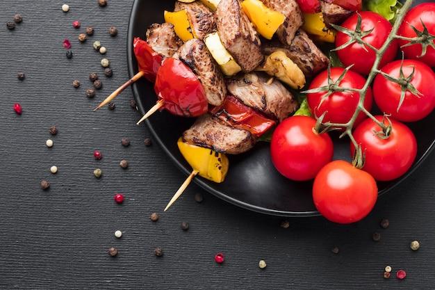 Вид сверху вкусного кебаба с помидорами на тарелке