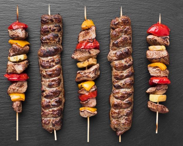 Вид сверху вкусного шашлыка с овощами и мясом