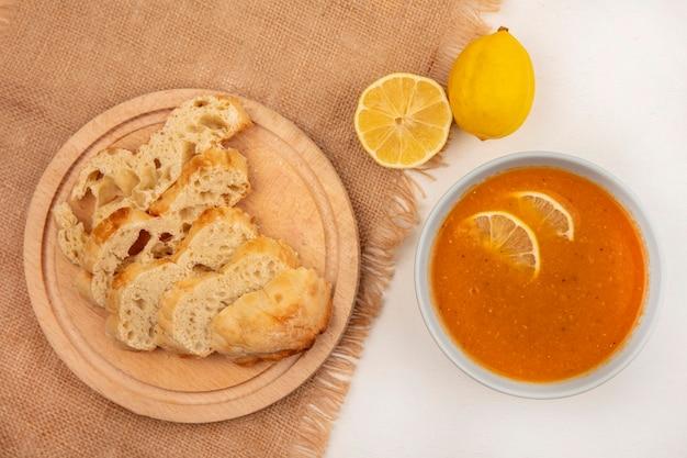 白い表面にレモンと袋布の上に木製のキッチンボード上のパンのスライスとボウルにおいしいレンズ豆のスープの上面図