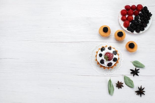 Вид сверху вкусного маленького торта со сливками и ягодным печеньем на белом, торт, бисквит, фрукты, сладкая сахарная ягода