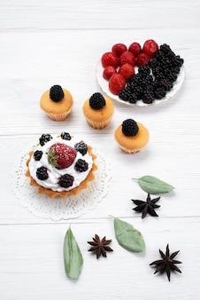 白い机の上のクリームとベリーのクッキー、ケーキビスケット焼きフルーツ甘い砂糖ベリーとおいしい小さなケーキの上面図