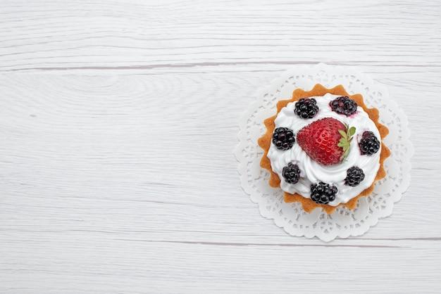 Вид сверху вкусного маленького торта со сливками и ягодами на белом, торт, бисквит, фрукты, сладкая сахарная ягода