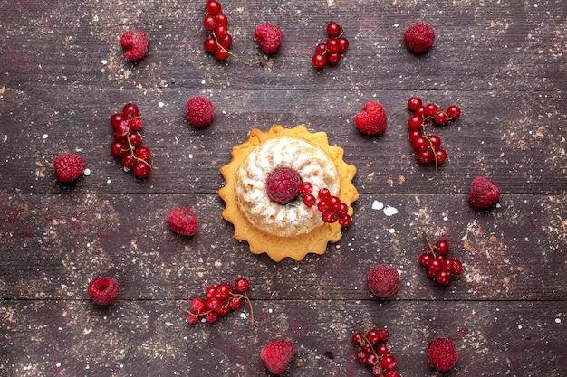 Вид сверху на вкусный маленький торт с сахарной пудрой и малиной, клюквой, коричневым, ягодным, фруктовым бисквитом