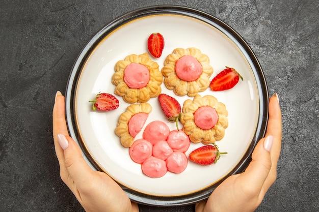 濃い灰色の表面のプレートの内側にピンクのクリームが入ったおいしい小さなクッキーの上面図